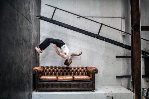 Performer above leather couch in warehouse